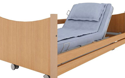 Light oak colour care bed in a profiled position with a profiled mattress