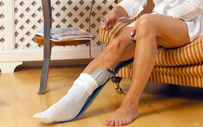 Person using a sock aid to lift a sock onto their right foot with ease
