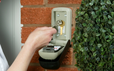 Keys being placed into a key safe that is attached to a brick wall